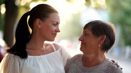 caregiver : Beautiful portrait of grandmother and her granddaughter look at each other with love on summer street. Sun flares. Girl embracing granny with gratitude. Family concept. 4k