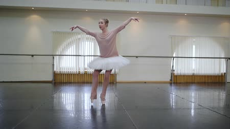 pirouette : Ballerina in white ballet tutu dress practicing in dance studio or gym. Woman dancing classical pas in class. Alone warming up before performance. Amazing dance. Slow motion Stock Footage