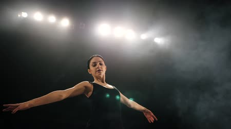ustalık : Young beautiful ballerina on smoke stage dancing modern ballet. performs smooth movements with hands against spotlights background. Woman in black costume on scene
