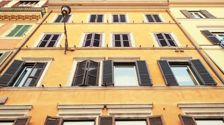 епископ : Apartment building streets in Rome. Windows with shutters. Facades of old houses in the streets of Italy. Traveling concept. Slow motion. Стоковые видеозаписи