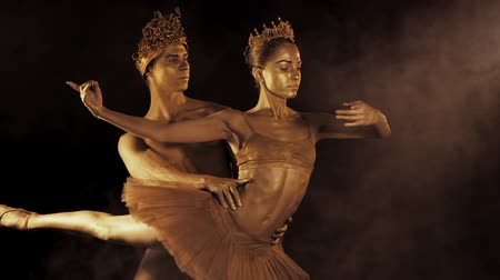 Professional, emotional ballet dancers with crowns on dark smoke scene performed by sexual couple king and queen with golden body art. Shining gold skin. Slow motion