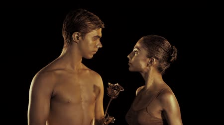 сексуальный : Professional ballet dancers on dark stage performed by sexual couple with golden body art. Shining gold skin. Man in love with girl presents her rose flower. Slow motion
