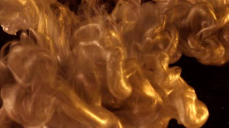 platina : Golden ink in water shooting with high speed camera. Gold drops of paint dropped, reacting, creating abstract cloud formations metamorphosis on black. Art backgrounds.
