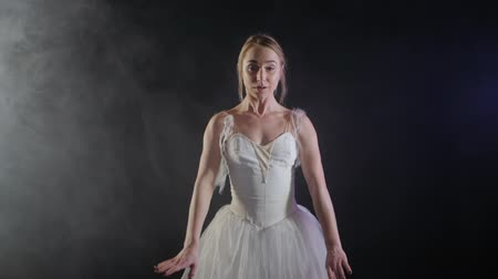 ustalık : graceful sensual ballerina in white tutu dress dancing elements of classical or modern ballet in the dark with light and smoke on the black background, slow motion