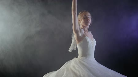 baletnica : Beautiful sensual ballerina in white tutu dress dancing elements of classical or modern ballet in the dark with light and smoke on the black background, slow motion