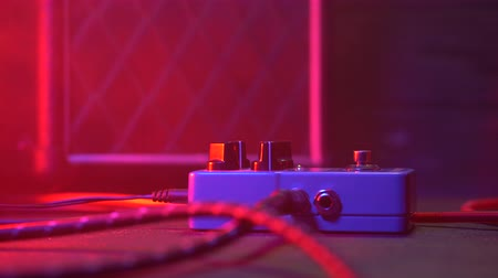 busking : Close up of guitar player or rock musician playing wah wah pedal on his show. Mans foot pressing on metal button for different sounds. Macro view. Neon light. 4k. Stock Footage