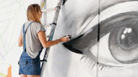 vandalismo : Beautiful girl making graffiti of big female face with aerosol spray on urban street wall. She standing on ladder. Creative art. Talented student in denim overalls drawing picture