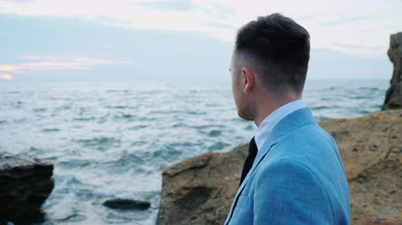 regaty : Portrait of young attractive business man or groom stands on sea shore with rocks and watching beautiful sunset or sunrise alone. 4k. Slow motion.