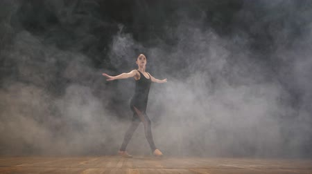 poddasze : Young beautiful ballerina on smoke stage dancing modern ballet in the dark. Woman in black costume performs on scene. Sensual amazing dance. Art concept