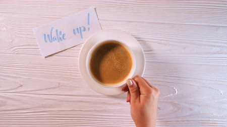 yetenekli : Wake up text. Font of lettering word on white paper with blue ink by calligrapher. Female hand takes cup of coffee from table. Morning, handwriting, lettering, concept.