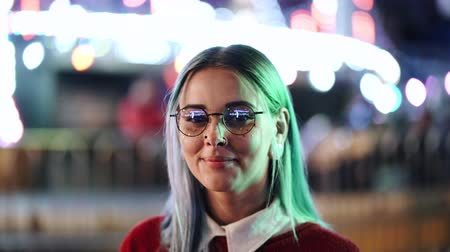 beckoning : Hipster girl with blue dyed hair and golden sequins as freckles. Woman with nose piercing, transparent glasses, ears tunnels, unusual hairstyle stands in amusement night park