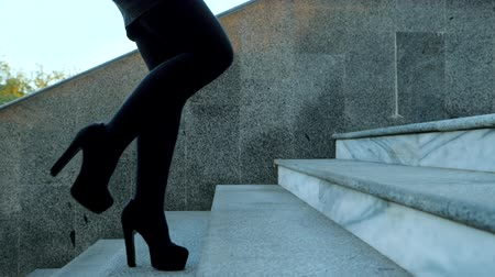 high heel shoe : Sexy legs with high black heels climbs stairs of city. Business woman walking on boulvard alone. Attractive girl in short dress at autumn season. Slow motion Stock Footage