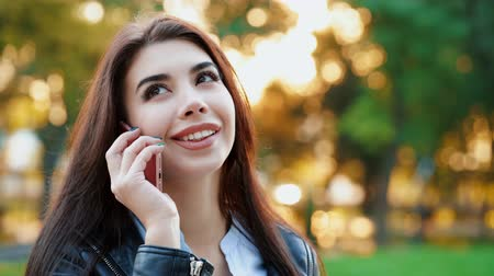 holding steady : Business woman with smartphone close up in autumn park in sunset light. Girl have conversation with cell phone. Beautiful caucasian young woman talking with mobile device. 4k.