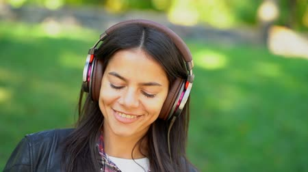 jovial : Happy mixed race young woman listening to music on headphones. Hispanic hipster girl dancing to rhythm and singing along melody in the park. Copy space.