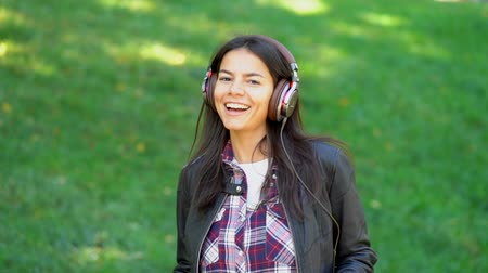 jovial : Happy mixed race young woman listening to music on headphones. Hispanic hipster girl dancing to rhythm and singing along melody in the park