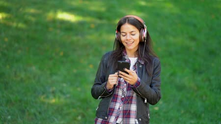 jovial : Beautiful mixed race young woman listening to music on headphones with smartphone. Hispanic hipster girl dancing to rhythm and singing along melody in the park.