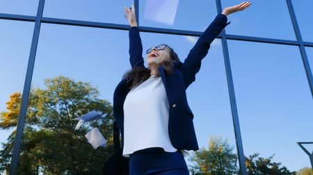 odchodu : Young businesswoman celebrates success and throwing papers and documents into air on modern office building background. Freedom, successful completion of project concept