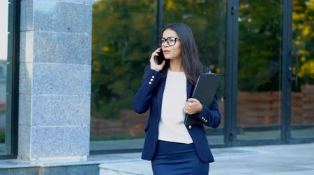 договориться : Businesswoman have conversation using mobile phone. Business girl in glasses and formal suit gladly talks with colleague. Office employee, wage worker, weekdays concept.