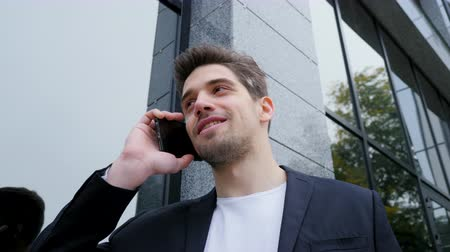 casual wear businessman : Businessman have conversation using smartphone. Business guy in suit jacket joyfully talks using cell phone. Office employee, technology concept. Camera moves from right to left Stock Footage