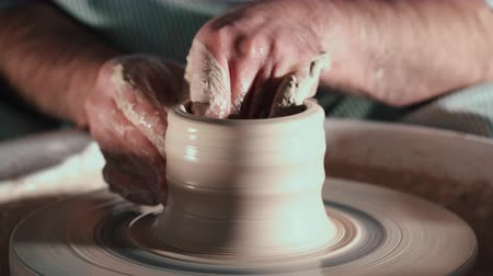 shaping : Creating earthenware and traditional pottery concept. Experienced male potters hands creating beautiful clay product - bowl - using professional tools. Toned cinematic, craft factory authentic Stock Footage