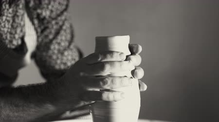 clay pot : Experienced potter shapes the clay product - jug - with pottery tools. Close up of male hands working on potters wheel. Shot of half-finished ceramic vase. Black and white tonned