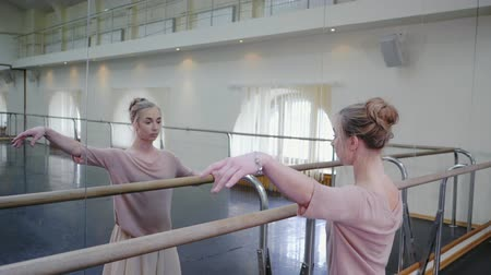 репетитор : Ballerina in beige sweatsuit and pointe stretches on barre in ballet gym. Woman standing near bar and mirror, preparing for performance or kneading before the lesson. Slow motion