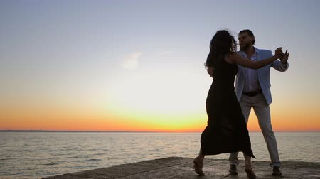 kuba : Portrait of young attractive couple dancing latin bachata near sea or ocean. Sunlight background. Summer time, romantic footage. Slow motion