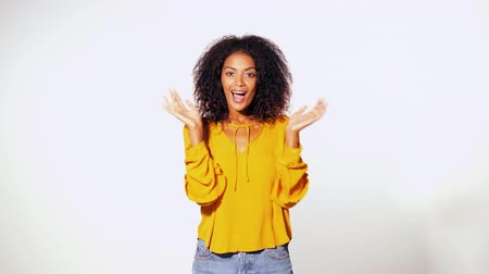 busto : Beautiful african american woman with afro hair in yellow wear smiling, pleasantly surprised to camera over white wall background. Cute mixed race girls portrait with amazement.