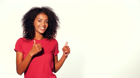 exibindo : Happy smiling african woman in red top presenting and showing something isolated on white background. Portrait of girl, she indicates with arms on her left with copy space.