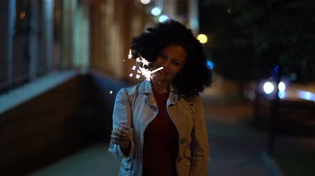 bochechudo : Young beautiful woman with very curly afro hair dancing with bengal fire at night illuminated street. Unusual trendy girl with sparklers. Holiday concept. Slow motion footage.