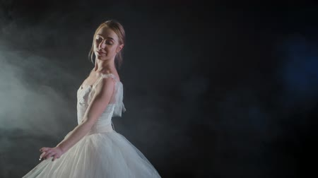 ustalık : graceful ballerina in white dress dancing elements of classical or modern ballet in the dark with light and smoke on the black background, slow motion