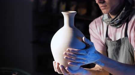 beeldhouwer : Craftsman creates jug. Man holding it in hands after spinning around on potters wheel. Product preparation for kilning. Focus on hands only. Small business, talent, inspiration concept