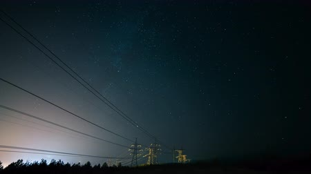 astro : Incredible night sky with stars, Milky Way passing over power line in long exposure timelapse. Beautiful panorama view. Nature in the countryside. Astro photography. Stock Footage