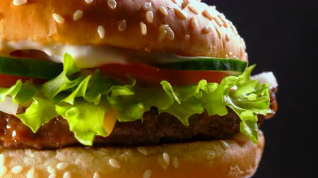 sajtburger : Fresh homemade grilled burger with meat patty, tomatoes, cucumber, lettuce, onion and sesame seeds. Yummy fast food concept. Unhealthy, junk food lifestyle. 4k