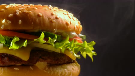 mosterd : Giant delicious fresh burger rotating on dark smoke background. Cheeseburger macro view. American fastfood, unhealthy fat yummy food concept.