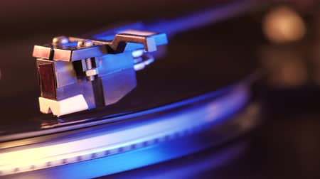 rock album : Record player turntable HD stock footage. A record player turntable with its stylus running along a vinyl record. Neon violet light.