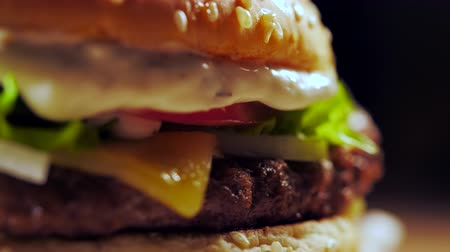 sajtburger : Big appetizing burger with meat cutlet, onion, vegetables, melted cheese, lettuce and mayonnaise sauce. Isolated hamburger rotates on dark smoke background, close-up view