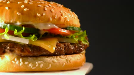american cuisine : Big appetizing burger with meat cutlet, onion, vegetables, melted cheese, lettuce and mayonnaise sauce. Isolated hamburger rotates on dark background, close-up view.