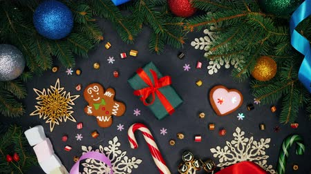 wrapping paper : Female hands puts gift wrapped in emerald paper with red ribbon on monochrome surface and then takes it. Black table with Christmas decorations - gingerbread, snowflakes, lollipops.Top plan view