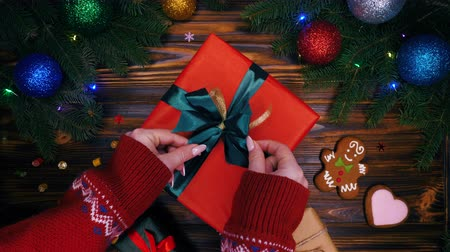 stylised : Hands in warm sweater puts gift in red paper and corrects green bow. Wooden vintage table with Christmas decorations - spruce branches, colorful balls, present boxes. 4k. Top view