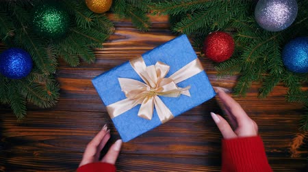 wrapping paper : Female hands puts gift wrapped in blue paper with bow on top on wooden table and then takes it. Christmas decorations - flashing garland lights, fir branches, bauble. Flat lay. Stock Footage
