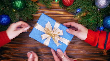 envolto : Couple exchanging Christmas present. Male hands in warm red sweater giving present in blue paper to his girlfriend or wife. Wooden table with new year decorations. Top plan view
