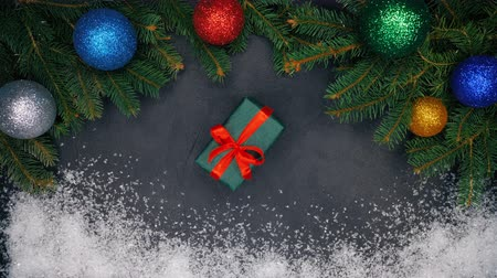 imbir : Womans hands puts gift wrapped in green paper in the center of frame made with fir branches and snow and then takes it. Christmas decorations - flashing garland lights, baubles Wideo