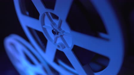 film camera : Old 8mm film projector showing film at night in dark room with blue light. Close-up of a reel. Slow motion. Vintage retro objects, cinematograph concept. Stock Footage