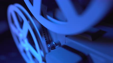 milimetre : Film projector with dramatic blue lighting and selective focus. Retro film production still life. Concept of film-making. Old 8mm projector is turning off. Close-up of a reel with a film.