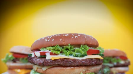 majonéza : Fresh homemade grilled burgers rotating on yellow background. Meat patty, tomatoes, cucumber, lettuce and sesame seeds. Yummy fast food concept. junk food lifestyle.