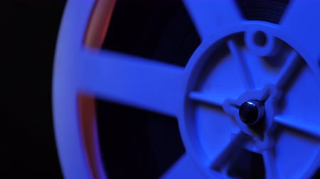 milimetre : Close-up of a reel. Old 8mm film projector showing film at night in dark room with blue light. Vintage retro objects, cinematograph concept