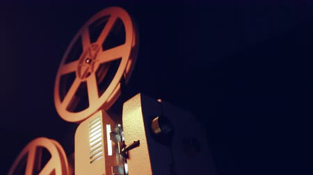 taŚma filmowa : Vintage objects, cinematograph concept. Retro film projector playing in the dark room. Old-fashioned antique super 8mm film projector projecting beam of light.