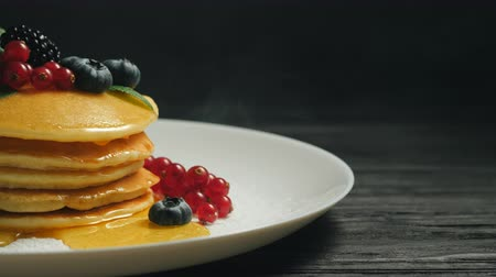 смородина : Fresh bakery. Pancakes with forest berries and honey on white plate and black smoke background. Copy space. Homemade healthy breakfast. Yummy food, dessert concept Стоковые видеозаписи
