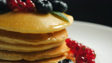 смородина : Stack of homemade pancakes or crepes decorated on top with forest berries - red currant  and blueberry. Delicious, healthy classic american breakfast. Side view. Close-up